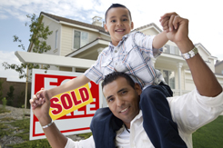 Hispanic Father and Son in Front of Their New Home with Sold Home For Sale Real Estate Sign.